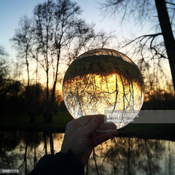 Cropped Image Of Person Holding Crystal Lens With Reflection Of Silhouette Trees At Dusk