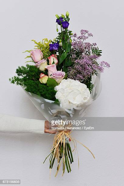 cropped image of person holding flowers bouquet against gray background - bouquet stock pictures, royalty-free photos & images