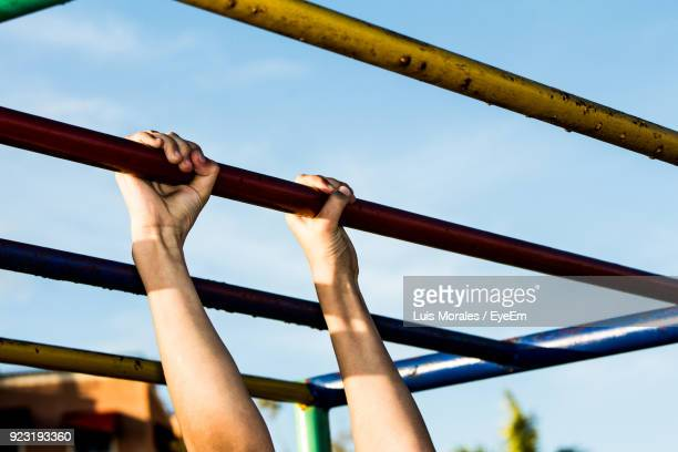Cropped Image Of Person Holding Horizontal Bar Against Sky
