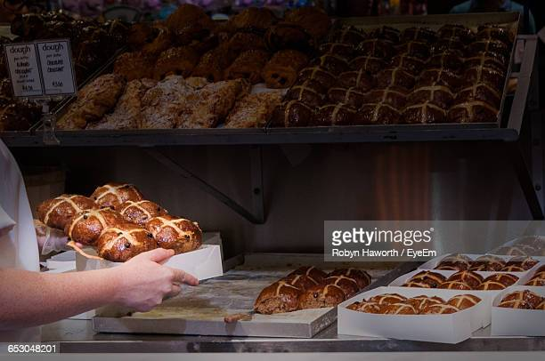 cropped image of person holding hot cross buns in bakery - hot cross bun stock pictures, royalty-free photos & images