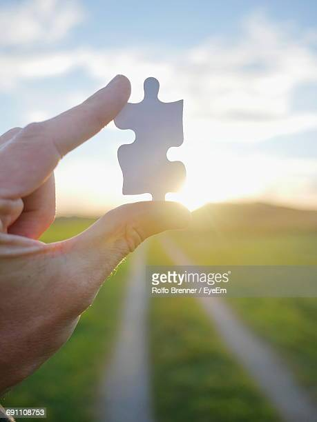 Cropped Image Of Person Holding Jigsaw Puzzle Piece During Sunset