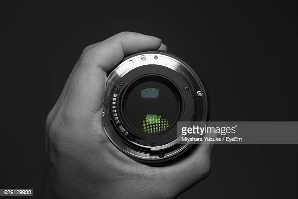 Cropped Image Of Person Holding Lens Against Black Background