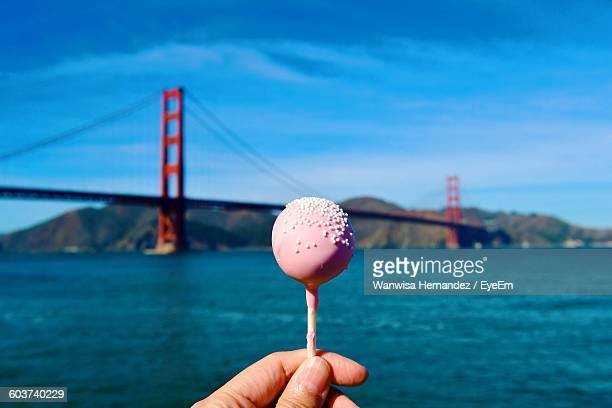 Cropped Image Of Person Holding Lollipop Against Golden Gate Bridge