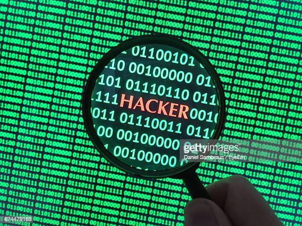 Cropped Image Of Person Holding Magnifying Glass While Looking At Hacker Text On Screen