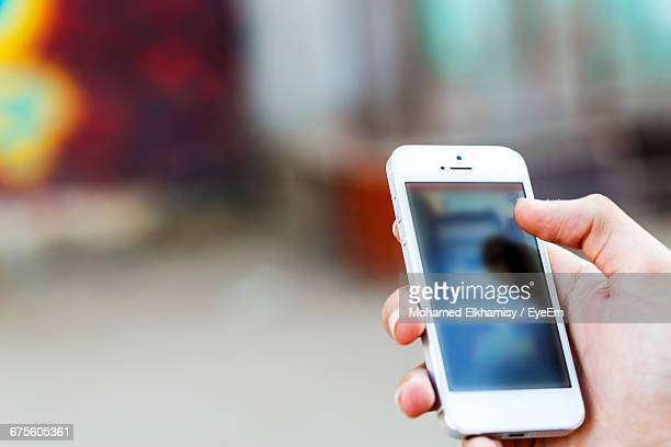 Cropped Image Of Person Holding Mobile Phone
