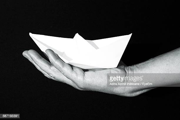 Cropped Image Of Person Holding Paper Boat Against Black Background