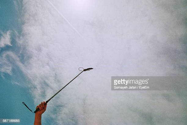 Cropped Image Of Person Holding Selfie Stick Against Cloudy Sky