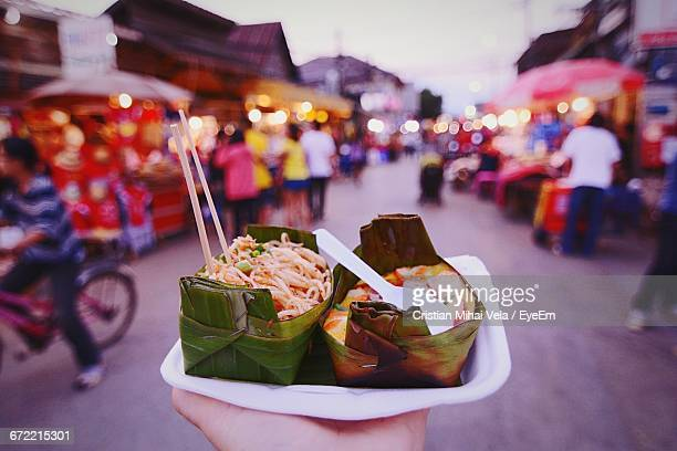 cropped image of person holding street food in market at dusk - street food stock pictures, royalty-free photos & images
