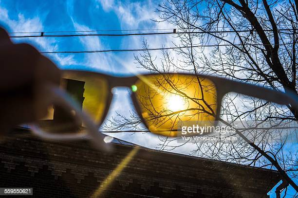 Cropped Image Of Person Holding Sunglasses Against Bright Sun