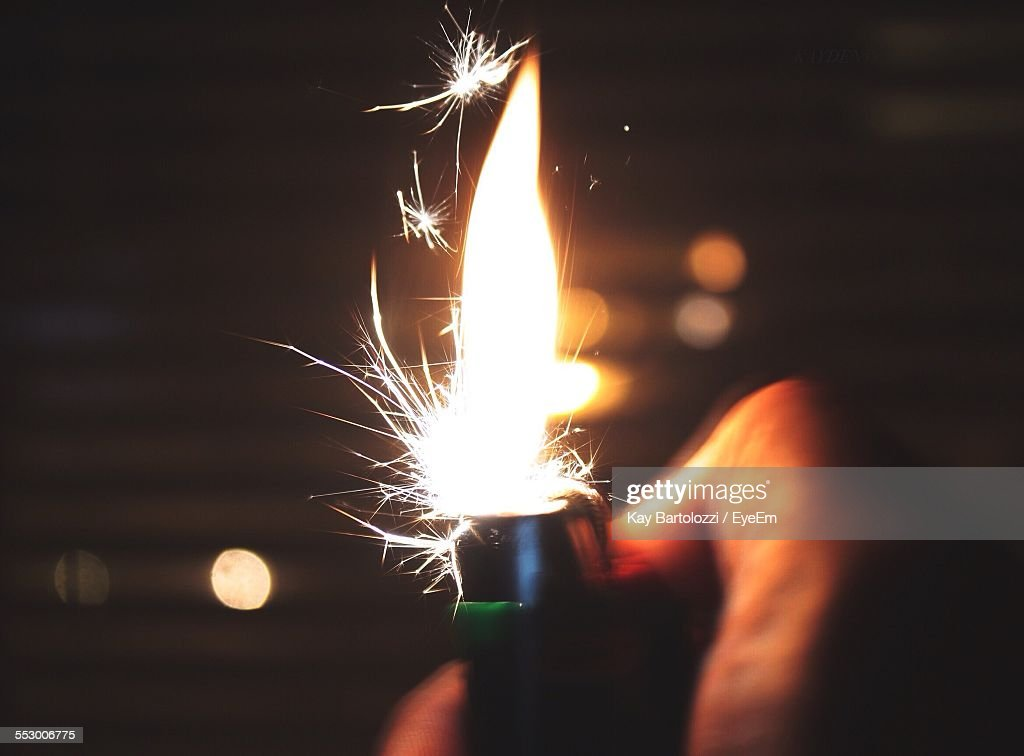 Cropped Image Of Person Igniting Cigarette Lighter : Stock Photo