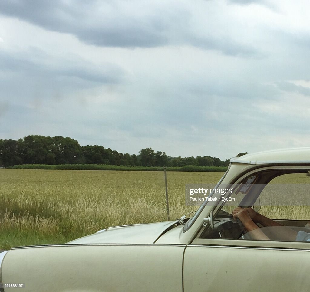Cropped Image Of Person In Car On Grassy Field Against Sky : Stockfoto