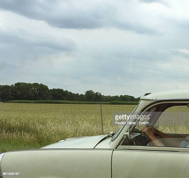 Cropped Image Of Person In Car On Grassy Field Against Sky