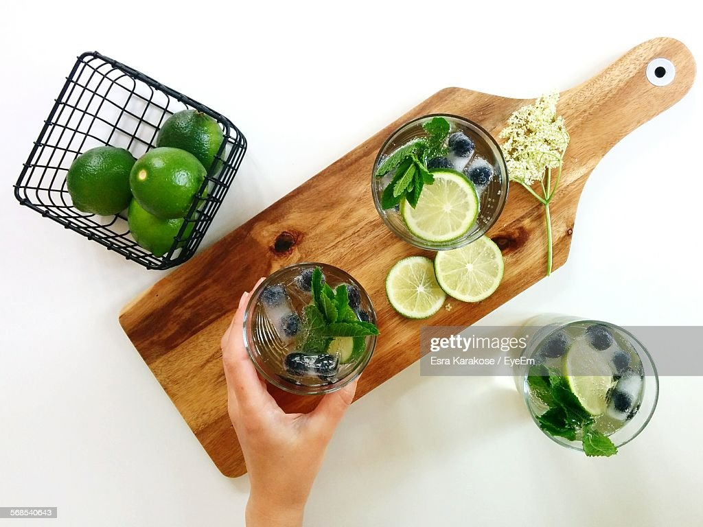 Cropped Image Of Person Keeping Drink On Cutting Board : Stock Photo