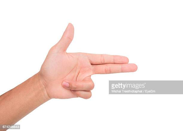cropped image of person making gun sign against white background - 銃 ストックフォトと画像