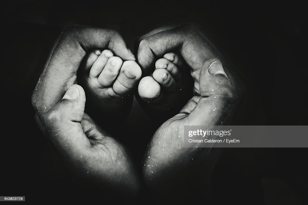 Cropped Image Of Person Making Heart Shape While Holding Baby Feet Against Black Background