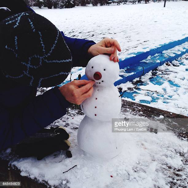 Cropped Image Of Person Making Snowman At Park
