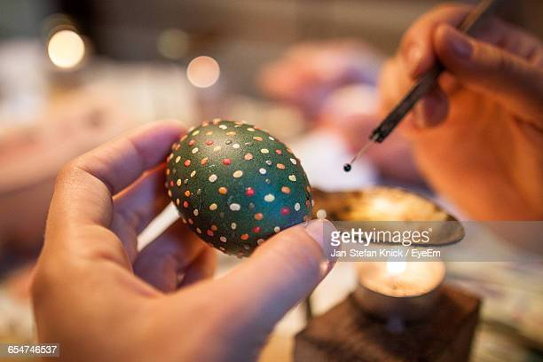 cropped image of person painting easter egg - osterfeuer stock-fotos und bilder