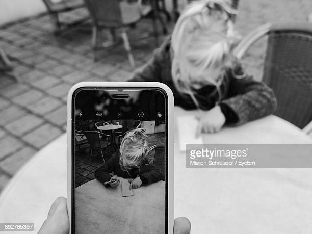 Cropped Image Of Person Photographing Girl With Writing On Notepad While Sitting At Sidewalk Cafe