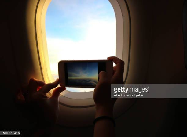 Cropped Image Of Person Photographing Sky Through Airplane Window