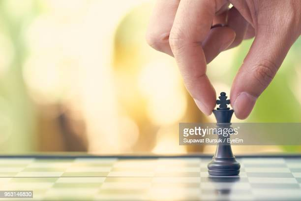 cropped image of person playing chess - chess piece stock pictures, royalty-free photos & images
