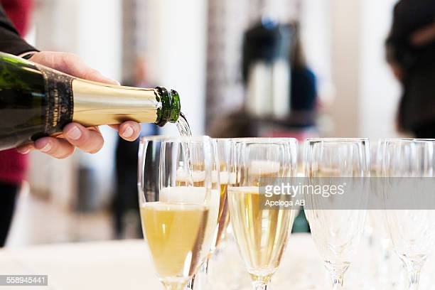 Cropped image of person pouring champagne in flutes
