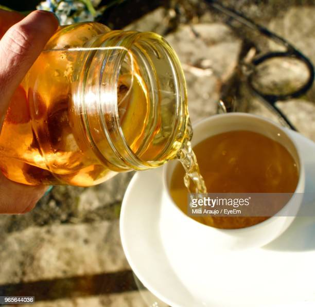 Cropped Image Of Person Pouring Herbal Tea In Cup