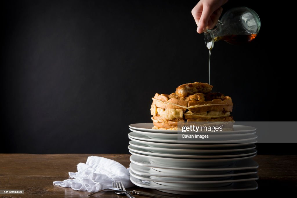 Cropped image of person pouring syrup on chicken and waffles : Stock Photo
