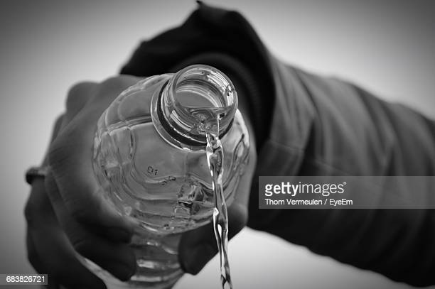 Cropped Image Of Person Pouring Water From Bottle