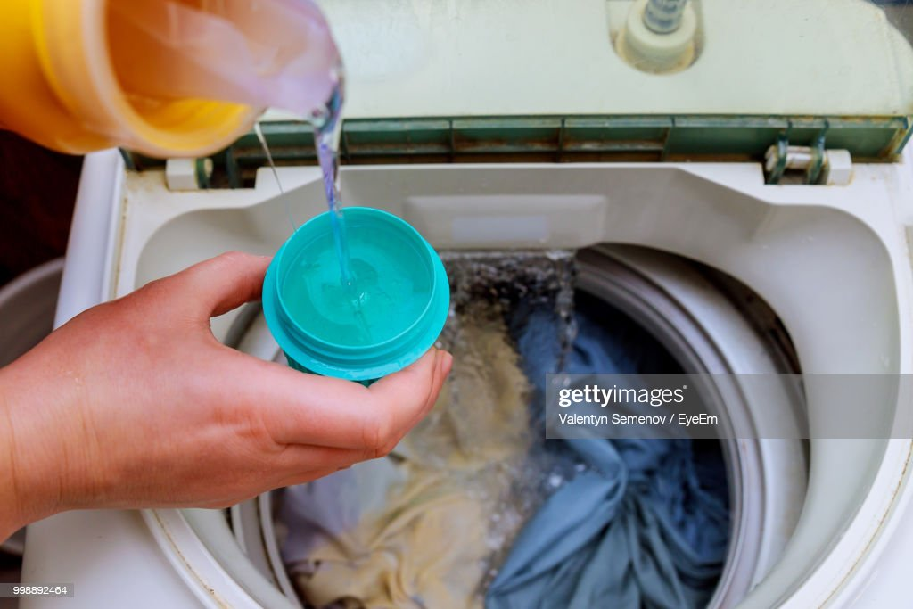 Cropped Image Of Person Pouring Water In Container Above Washing Machine : Stock Photo