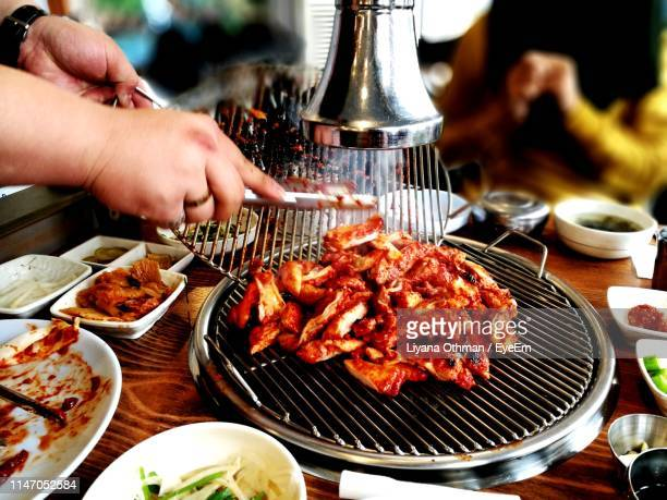 cropped image of person preparing food on barbecue grill at restaurant - korea stock pictures, royalty-free photos & images