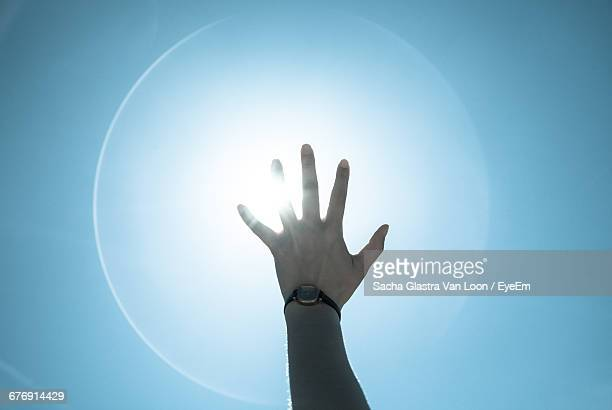 cropped image of person reaching towards bright sun - corona sun stock pictures, royalty-free photos & images