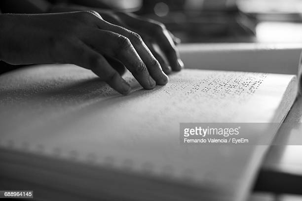 cropped image of person reading braille - assistive technology stock photos and pictures