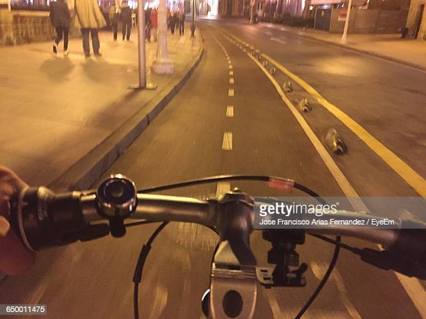 cropped image of person riding bicycle on illuminated street at night - gijon fotografías e imágenes de stock