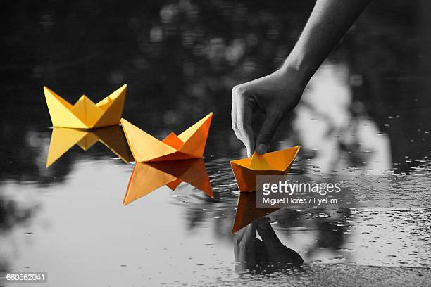 cropped image of person sailing orange paper boat on puddle - isolated color stock pictures, royalty-free photos & images