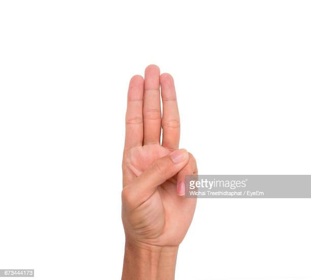Cropped Image Of Person Showing Three Fingers Against White Background