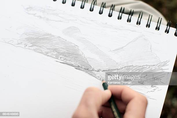 Cropped image of person sketching on paper