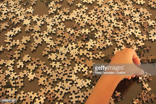 Cropped Image Of Person Solving Puzzle On Floor