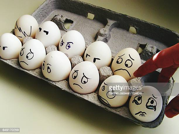 Cropped Image Of Person Touching Eggs With Smiley Faces In Crate At Table