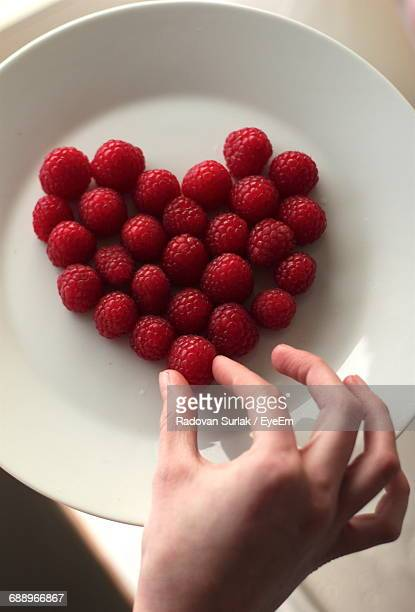 Cropped Image Of Person Touching Raspberries In Heart Shape