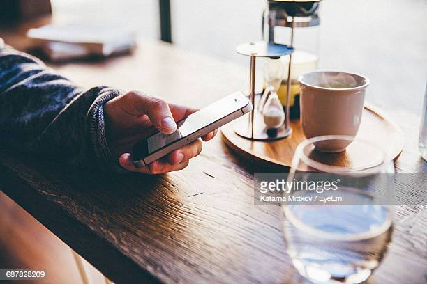 Cropped Image Of Person Using Mobile Phone By Tea Cup On Table