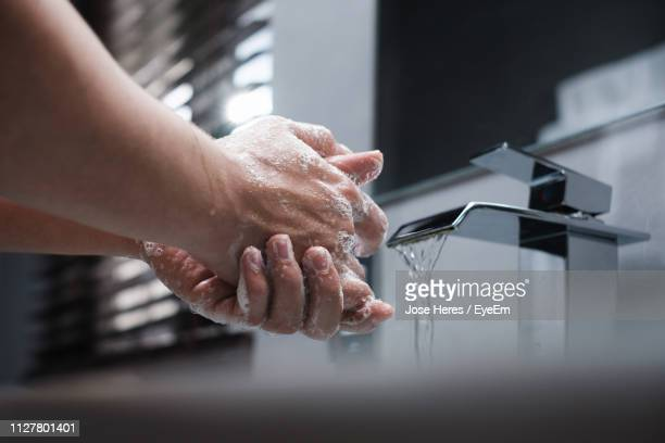 cropped image of person washing hands at home - hygiene stock-fotos und bilder