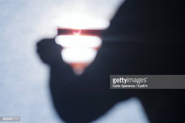 Cropped Image Of Person Watching Solar Eclipse Through Negative Film At Night