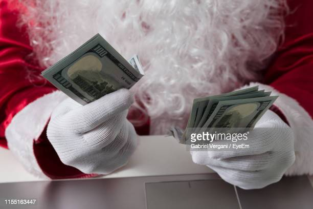 cropped image of person wearing santa costume while holding paper currencies - christmas cash stock pictures, royalty-free photos & images