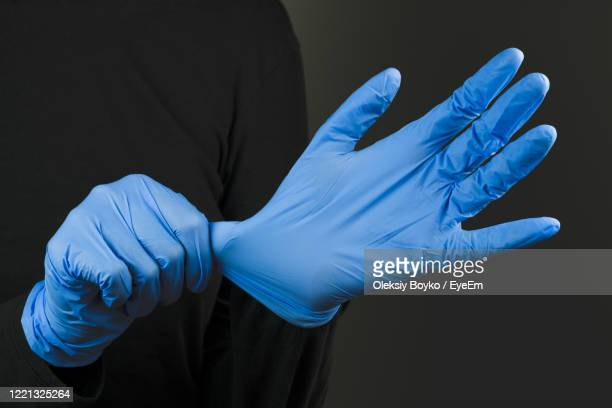 cropped image of person wearing surgical glove - surgical glove stock pictures, royalty-free photos & images