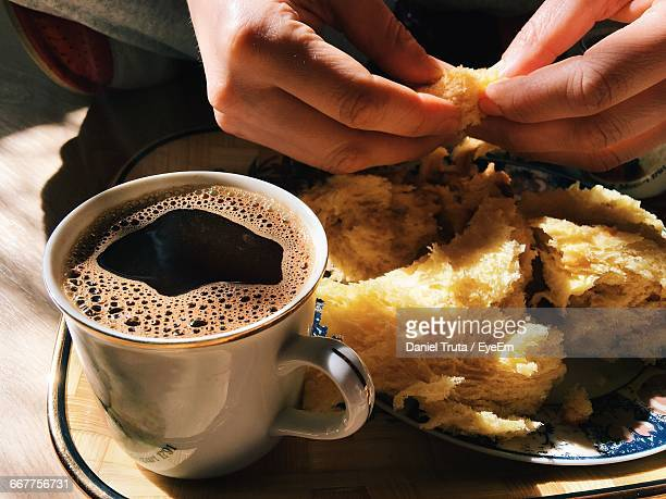 cropped image of person with black coffee and panettone - panettone foto e immagini stock