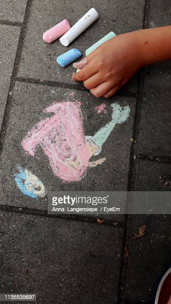 Cropped Image Of Person With Chalk Drawing On Walkway