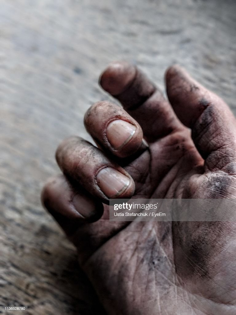 Cropped Image Of Person With Dirty Hand On Wooden Table : Stock Photo