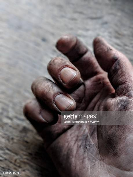 Cropped Image Of Person With Dirty Hand On Wooden Table