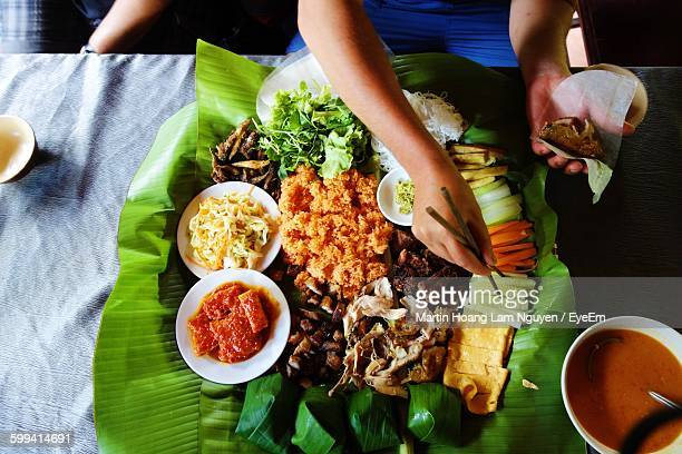 Cropped Image Of Person With Meal On Banana Leaf