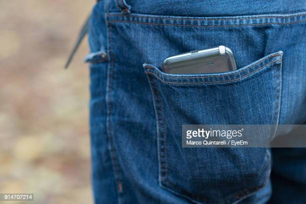 cropped image of person with mobile phone in pocket - pocket stock photos and pictures
